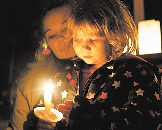 Cara Kowalczyk, left, and Michelle Peterson, 4, of Lordstown, reflect on the victims of Friday's Newtown, Conn., elementary school massacre. The two attended a vigil in Founder's Park in Lordstown on Sunday evening.