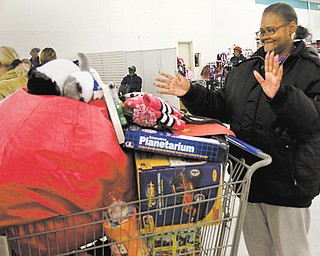 Vickie Adkins of Youngstown shops for Christmas gifts for her grandchildren, Kei'Sean, Nakaia and Tre'Sean McRae, at the Mahoning County Salvation Army gift distribution. About 2,000 children from 1,500 families are slated to receive Christmas gifts through the program, which continued today for preregistered families.