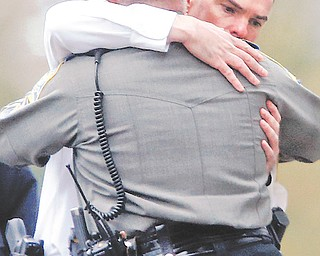 Police officers console each other outside the funeral service for 6-year-old Noah Pozner in Fairfield, Conn., on Monday.
