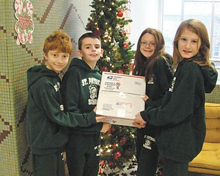 Students at St. Patrick School in Hubbard have continued their tradition of giving by adopting two local soldiers serving overseas this holiday season. The students collected items the soldiers need for everyday life and special treats to make their time away from home a little easier. The students send the soldiers packages throughout the school year. From left, Simon Yesh, Cooper Muccio, Regan Sandy and Alexis Chiandussi are holding a package that is ready to mail to the soldiers.