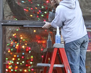 William d Lewis The Vindicator  Anthony Palumbo gen mgr of Dooneys Sports Bar, washes windows infront of his establishment as city Christmas Tree is reflected in window.