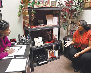From left, Kim Hamilton, a life coach at Hams Beauty & Barber in Liberty, talks with Symone Hurt, one of her  and barbers finish up customers and offer life coaching, all under one roof.