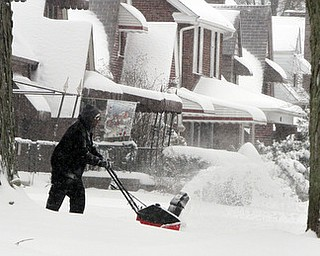 William D LEwis The vindicator  Brandon fleming uses a snowblower ot clear his drive along Euclid in Boardman Wed afternoon.