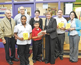 Struthers Rotary continues to participate in the dictionary project with local schools. Students in third and fourth grades at Campbell, Lowellville, St. Nicholas and Struthers schools will receive dictionaries. More than 3,000 dictionaries have been distributed since the program began. In front is Rotarian Lisa Daprile shown presenting dictionaries to Le'Asia Gibbs, left, and Zachary Luciano, who represent the third- and fourth-graders at Campbell Elementary. In the second row are Rotarians Paul Paris, left, and Tom Baringer, Campbell Elementary teacher Lori Ladigo, Rotarian Bryan Higgins and Campbell Elementary teacher Annette Tovarnak.