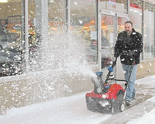 Jared Pekar, sales manager at Do Cut in Boardman, uses a snow blower in front on his store along state Route 224. Area retailers credit Wednesday's storm for a spike in the sale of such machines.