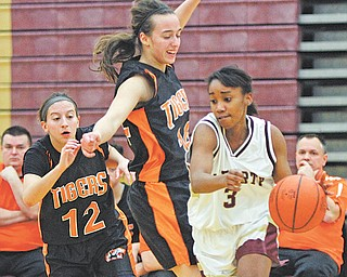 Liberty's Shamara Golden (3) tries to drive around Newton Falls defenders Brooke Barreca (14) and Alissa Abraham (12) during the first half of their All American Conference basketball game Thursday at Liberty High School. The Tigers downed the Leopards, 59-30.
