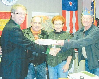 Funds to benefit needy veterans and their families were raised at the annual reverse raffle and basket auction sponsored by Catholic War Veterans Post 1292 of Youngstown. Mark Bell, left, director of the Veterans Clinic on Belmont Avenue, and Lori Stone, clinic volunteer, accepted the $1,200 donation from Al Bisker, second from left, Post 1292 trustee and Gary Barnes, post commander.