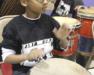 William D Leiws the Vindicator  Isaiah Carter, 9, member of Harambee drum corp plays during KwanzaacelebrationTuesday at McGuffey Centre.