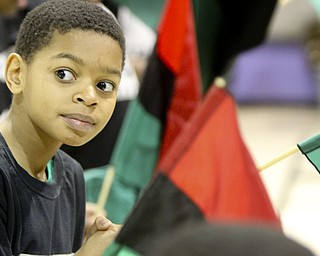 William D Leiws the Vindicator Tyler Wagner,11, holds an african flag during Kwanzaa celebration Tuesday at McGuffey Centre.