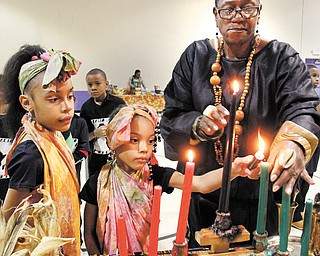 Lynnette Kimako Miller, right, a local Kwanzaa event coordinator, watches as Mercedes Dykes, 8, left, and her sister and Aniaya, 6, light candles during the final day of Kwanzaa. The McGuffey Centre hosted an event Tuesday on the final day of the seven-day holiday.