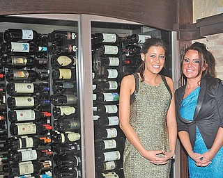 Hostesses Kolbie Foust, left, of Girard and Aimee Creatura of Hartford are shown in front of D'Vino's wine cellar.