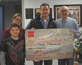 """Wells Fargo Advisors announced a $3,000 grant to Second Harvest Food Bank to help fund """"Feed Our Community"""" in the Mahoning Valley. The announcement was made earlier this month. The grant is one of nearly 300 basic needs grants made throughout the United States by the company to build strong communities and improve quality of life to make a positive difference. Shown holding the oversized check are Susan Roach, left, client associate, and her son, Trent; David A. Croutch, branch manager of Wells Fargo Advisors; and Michael Iberis, executive director of Second Harvest Food Bank of the Mahoning Valley. Photo: Special to The Vindicator"""