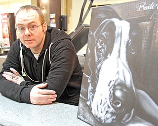 Josh Shaull, owner of Airtistix Airbrush in Eastwood Mall, displays his painting of a Great Dane named Baxter. At top, Shaull airbrushes details on a T-shirt.