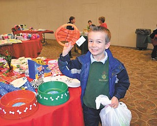 Aidan Markey, a first-grader at Holy Family School in Poland, picks out a gift for his pet during a Santa's Workshop at the parish center.