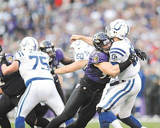 Indianapolis Colts quarterback Andrew Luck is hit by Baltimore Ravens outside linebacker Paul Kruger as right guard Mike McGlynn, a graduate of Austintown Fitch High, blocks during the second half of their AFC wild card playoff game Sunday. The Ravens won, 24-9.