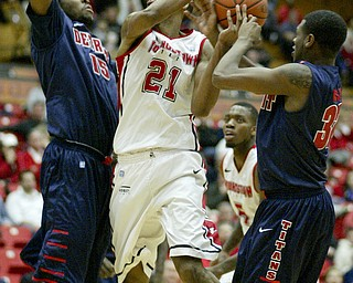 William D Lewis the Vindicator YSU's Damian Eargle(21) is hemmed in by Detroits Ugochukwu Njoku(15) and Anton Wilson (32) during 1rst half action Thursday 1-9-13 at YSU.