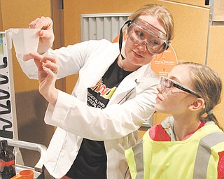 Holly Eberly, 11, right, a member of Girl Scout Troop 80420, of Canfield, watches Audra Carlson, OH WOW! education manager, during a science program at OH WOW! The Roger & Gloria Jones Children's Center for Science & Technology in downtown Youngstown.
