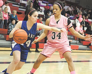 "Poland's Rachael Robertson (14) tries to get past Fitch defender Briana Edwards (34) during the Falcons' fourth annual ""Think Pink Game"" on Thursday at Fitch High School in Austintown. The Falcons defeated the Bulldogs, 46-25."