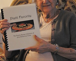 Yole Conte of Austintown holds the cookbook she put together with old family recipes handed down from generation to generation.