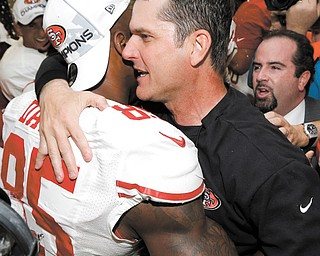 San Francisco 49ers head coach Jim Harbaugh, right, hugs Vernon Davis after defeating the Atlanta Falcons on Sunday in the NFC Championship game in Atlanta.