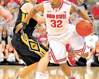 Ohio State's Lenzelle Smith (32) moves the ball past Iowa's Mike Gesell during the second half of a game Tuesday in Columbus. Ohio State won 72-63.