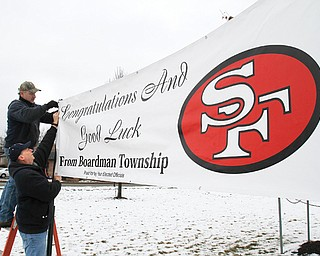 Mike Hardie and Ron Gorski hang up a banner supporting the San Francisco 49ers on Monday in front of the Boardman Township Government Center on Market Street. The banner was paid for out-of-pocket by township trustees. The 49ers take on the Baltimore Ravens on Sunday in the Super Bowl.
