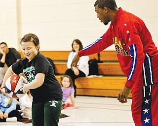 """Anthony """"Buckets"""" Blakes of Phoenix, Ariz., a member of the world-renowned Harlem Globetrotters, teaches Lauren Ladd, a fourthgrader, some ball-handling moves. Blakes also conducted an anti-bullying prevention program for the children Monday at St. Patrick Parish Center, Hubbard."""