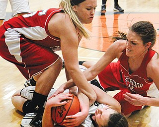 From left, Columbiana's Khylea Fullum, Lowellville's Rachel Durbin and Columbiana's Megan Cutlip wrestle for the basketball during Monday's showdown.