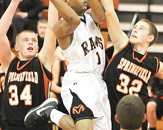 Springfield's Jared McTigue (32) tries to block Mineral Ridge's Corey Phillips (1) during an Inter Tri-County Tier One game Tuesday in Mineral Ridge. The Tigers edged the Rams in overtime, 58-54.