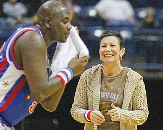 """The Harlem Globetrotters' """"Big Easy"""" Lofton (52) wipes the sweat off his face before getting a kiss from fan Denise Stoneman of Boardman during Wednesday's exhibition basketball game against the Global Select at the Covelli Centre in Youngstown."""