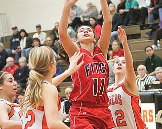 Austintown Fitch's Megan Sefcik (11) goes up for two between Howland's Gabby Cvengros (22) and Jordan Entler (12). Sefcik scored her 1,000th point Thursday at Howland.
