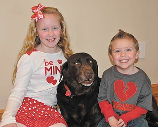 Preslie, left, and Vander, right, are decked out in their Valentine's Day gear with Hunter the dog. They're all from Poland.