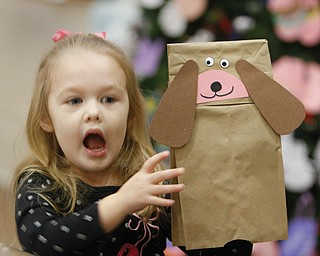 """Gianna Page, 3, of Poland shows off the puppet dog she made at the Poland Branch of the Public Library of Youngstown and Mahoning County. She was taking part in the """"Baby Brilliant: Tales and Talk for 2s and 3s"""" program at the library. At top, Vikki Peck, children's librarian, reads a story while below, Emily Swantek, 3, and her baby sitter, Jyl Willoughby, pay attention during the program."""