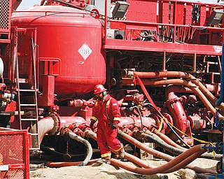 An unidentified worker steps through the maze of hoses being used at a remote fracking site being run by Halliburton for natural-gas producer Williams in Rulison, Colo. The oil and gas industry is trying to ease environmental concerns by developing nontoxic fluids for the drilling process known as fracking.