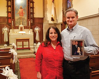 The Rev. Susan Brown and her husband, the Rev. Jerry Krueger, pastor of Trinity United Methodist Church, 30 W. Front St., Youngstown, are shown in the Chapel of Friendly Bells. He's holding their wedding photo from Feb. 20, 2010. The clergy couple will perform walk-in weddings and vow renewals on Valentine's Day, Feb. 14, in the downtown chapel. Couples must have marriage licenses and identification.