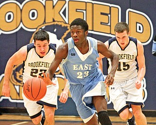 Brookfield's Ryan Mosora (22) and Jeremy Quinlan (15) pursue East High's Taylor Johnson (23) as Johnson breaks away down the court during Tuesday's basketball game at Brookfield High School. The Panthers defeated the Warriors, 75-62.