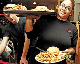 Kesha Rhodes, waitress at Bogey's Bar & Grill, delivers meals to the Burger Guyz.