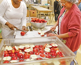 Shauna Spencer, left, and Mary Flores wash, cut and prepare thousands of apples for elementary school students' lunches at the Youngstown City Schools' central kitchen at Choffi n Career and Technical Center. The district bought the apples, which were grown in Greenford through the Lake-to-River Food Cooperative with the help of a grant.