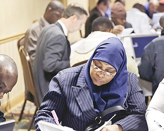 Karina Abdul-Haqq of Newark, N.J, center, completes a job application at a job fair sponsored by Swissport in Newark, N.J. The Labor Department reported Thursday that weekly applications for unemployment benefits fell 5,000 to a seasonally adjusted 366,000 last week.