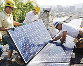 California Green Design employees assemble solar electrical panels on the roof of a home in Glendale, Calif. Homeowners on the hunt for sparkling solar panels are lured by ads filled with images of pristine landscapes and bright sunshine, and words about the technology's benefits for the environment. However, the industry is creating millions of solar panels each year and, in the process, millions of pounds of polluted sludge and contaminated water.