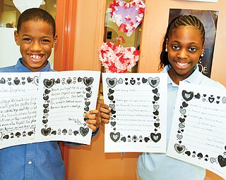 Tavan Sallie, left, and Kamille Moore, fourth graders at Youngstown's Taft Elementary School, show off the valentines they wrote and sent to soldiers at the Department of Veterans of Affairs Medical Center in Pittsburgh's Post Traumatic Stress Disorder Clinic.