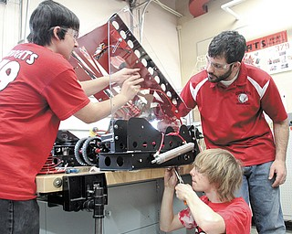 Austin Wagner, left, a sophomore at Girard High School, and senior Sam Horne, center, assemble parts for the RoboCats' new robot under the supervision of Ashraf Hadi , team adviser. The school's robotics team has been working for six weeks to build its new robot, which will compete beginning in March.
