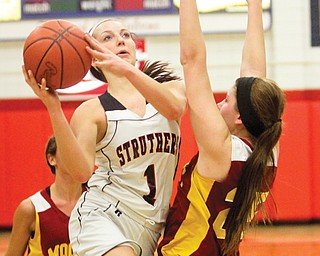 Struthers' Ashleigh Ryan (1) drives to the hoop around Cardinal Mooney's Nichole Webber (25) during their Division II sectional semifinal basketball game Monday at Austintown Fitch High School. The Wildcats downed the Cardinals, 55-27, and will face Crestwood on Thursday.