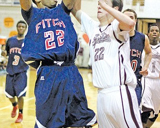 Quincy Higgins of Fitch goes for the jumper against Boardman's Dylan Bosela during the third quarter of their game Tuesday in Boardman. The Falcons defeated the Spartans, 35-25.