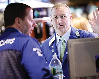 Traders work on the floor at the New York Stock Exchange in New York on Tuesday, when talk of more mergers and acquisitions sent stock prices higher.