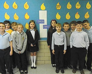 Fourth-grade students of Holy Family School are standing in front of the Lumen Christi bulletin board. They are, from left in front, Steven Hiner, Caitlin Palusak, Jacob Shogren and Patrick Assion; and, in back, Dominic DeToro, Patrick Howlett, Ava Szalay, Augusta Fox, Payton McMahon, Brian White and Matthew Ranno. The board was designed by fourth-grade teacher Kathy Holsinger to make students and families aware of Catholic identity and faith infused with learning. The new Lumen Christi Catholic School System includes Catholic elementary schools in the Mahoning Valley. In Latin, the name means Light of Christ and is put into practice through daily prayer, regular liturgy participation and the compassion students demonstrate through varied service projects.