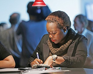 An unidentified woman answers questions on a job application at a job fair in Sunrise, Fla. The number of Americans seeking unemployment benefits jumped 20,000 last week to a seasonally adjusted 362,000, though it remains at a level that suggests slow but steady improvement in the job market.