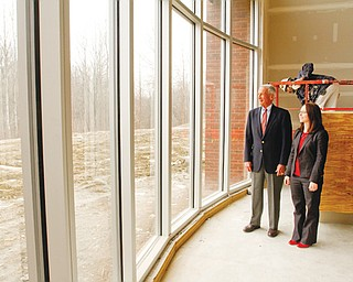 Dr. David Ritchie, president of the board of trustees of the Public Library of Youngstown and Mahoning County, tours the new Jackson-Milton public library under construction on Mahoning Avenue in Jackson Township. With him is Heidi Daniel, director of the library system.