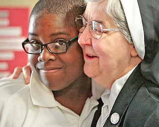 Sister Mary Dunn, principal of Youngstown Community School, gives a congratulatory hug to Demar Brown after the student performed well on a test.