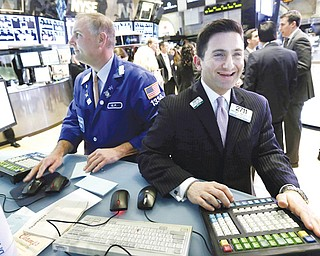 Specialist Christian Sanfillippo, right, smiles as he works at his post on the floor of the New York Stock Exchange. The Dow's new all-time high and better economic data from the United States propelled world stock markets higher Wednesday.